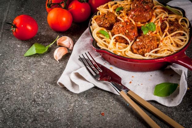Spaghettiteigwaren mit fleischklöschen, basilikumtomatensauce in der roten roheisenwanne, auf schwarzer steintabelle Premium Fotos