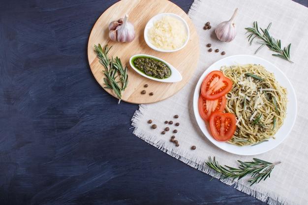 Spaghettiteigwaren mit pestosoße, tomaten und käse auf einer leinentischdecke auf schwarzem hölzernem hintergrund. Premium Fotos