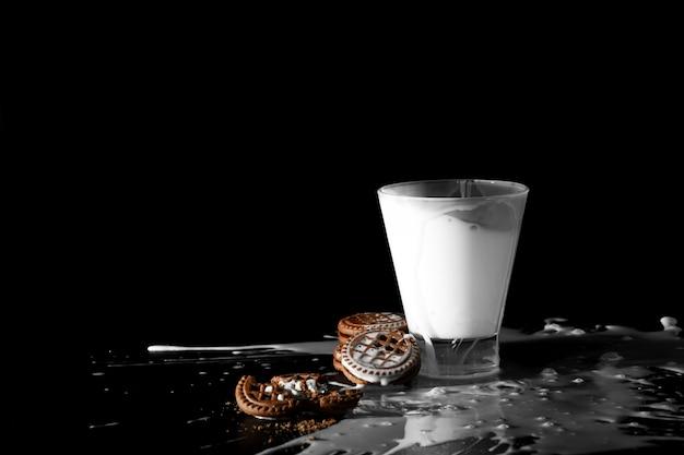 Spalsh im glas milch- und schokoladenplätzchen auf schwarzem Premium Fotos
