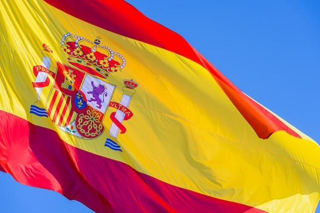 Spanien-flagge mit dem königlichen schild, das in den wind auf hintergrund des blauen himmels wellenartig bewegt Premium Fotos