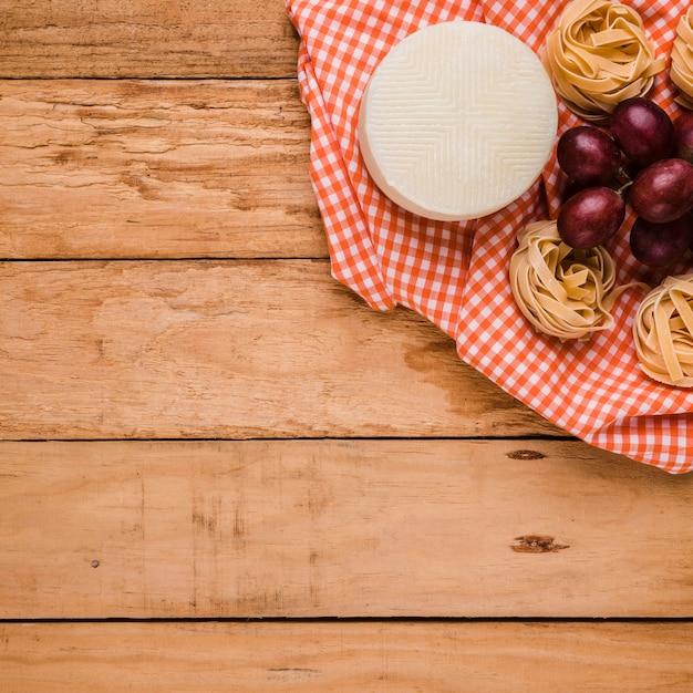 Spanischer manchego-käse; rote trauben und rohe teigwarenbälle über karierter tischdecke auf hölzernem schreibtisch Kostenlose Fotos