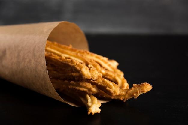 Spanischer snack von churros in einem packpapier Kostenlose Fotos