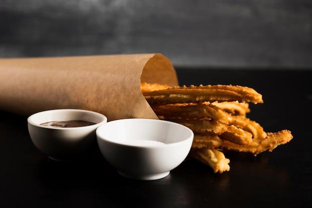 Spanischer snack von churros und tassen mit geschmolzener schokolade und zucker Kostenlose Fotos