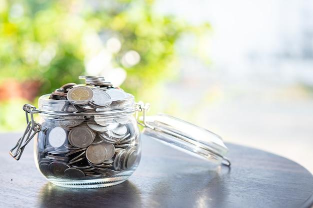 Sparen sie geldmünzen im grasglas, geschäftsfinanzierungsinvestitionskonzept. Premium Fotos