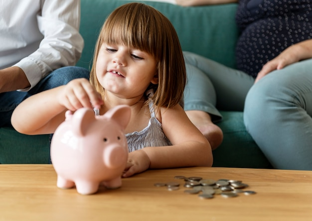 Sparendes geld der familie im sparschwein Kostenlose Fotos