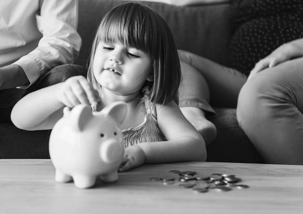 Sparendes geld der familie in einem sparschwein Kostenlose Fotos