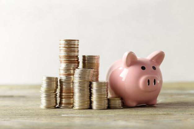 Sparschwein mit münze auf altem holztisch Premium Fotos