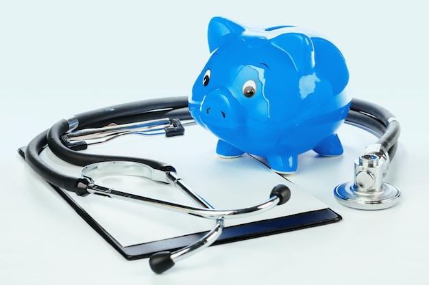 Sparschwein und stethoskop lokalisiert auf einem weiß Premium Fotos