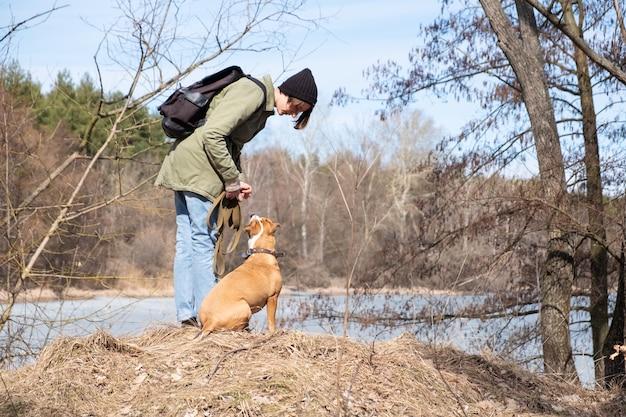 Spazierengehen und hund in freier wildbahn unterrichten. frau, die mit ihrem hund am wald durch den fluss, zufällige und wandernde art sich verständigt Premium Fotos