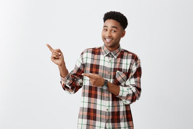 Speicherplatz kopieren. junger dunkelhäutiger afrikanischer fröhlicher kerl mit afro-frisur im karierten hemd, das mit händen auf weißer wand mit glücklichem und aufgeregtem ausdruck beiseite zeigt Kostenlose Fotos