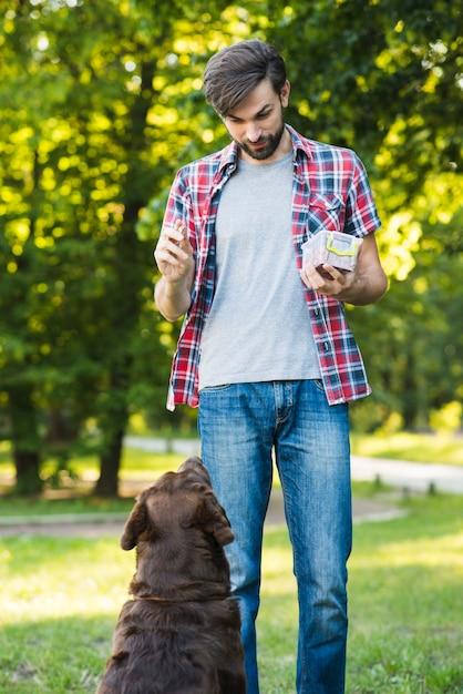 Speisenfutter des mannes zu seinem hund im garten Kostenlose Fotos