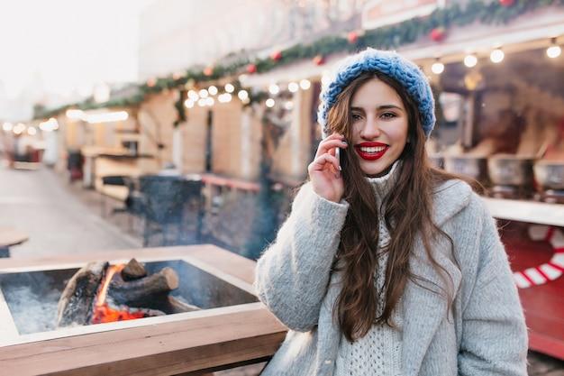 Spektakuläre brünette frau im grauen wollmantel, der am weihnachtsmarkt mit lächeln aufwirft. romantisches mädchen mit langer frisur trägt blauen hut, der auf straße steht, die für winterferien verziert wird. Kostenlose Fotos