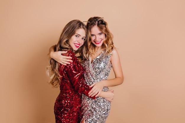 Spektakuläre dame, die schwester mit zärtlichkeit umarmt und weihnachtsfeier genießt Kostenlose Fotos