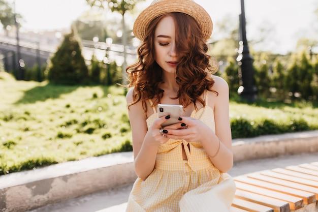 Spektakuläre junge dame in der trendigen hut-sms-nachricht beim sitzen im schönen park. foto im freien von modischem mädchen mit ingwerhaar, das jemanden auf bank wartet. Kostenlose Fotos