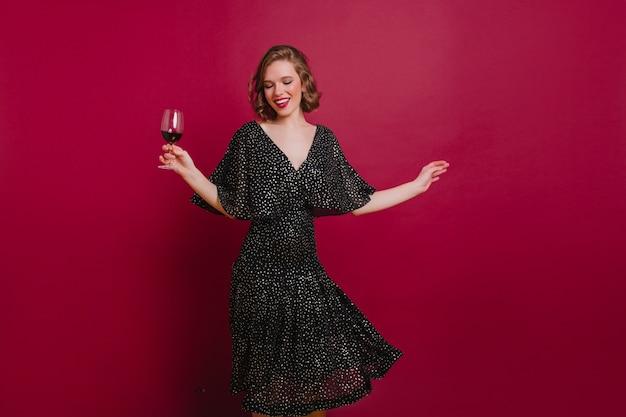 Spektakuläres weibliches modell, das unten beim tanzen auf der party schaut Kostenlose Fotos