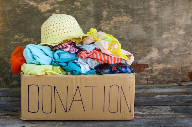 Spendenkasten mit sommerkleidung auf dem alten hölzernen hintergrund. Premium Fotos