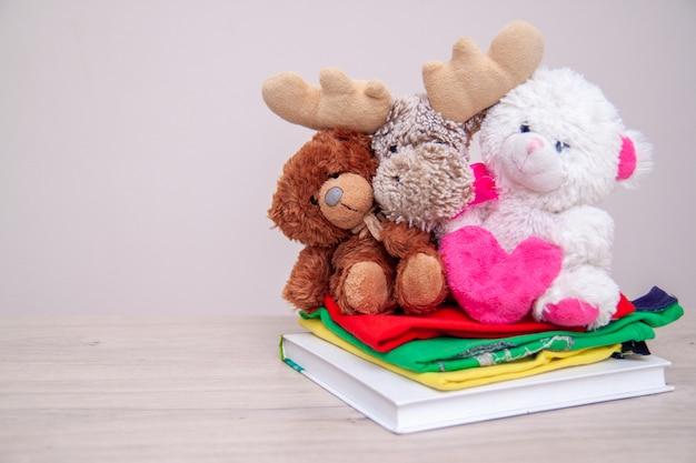 Spendenkonzept. spendenbox mit kinderkleidung, büchern, schulmaterial und spielzeug. teddybär mit großem rosa herzen in den händen. Premium Fotos