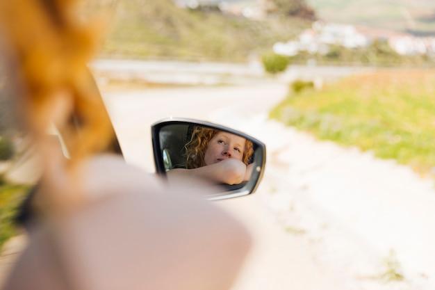 Spiegelbild des weiblichen reitens im auto Kostenlose Fotos