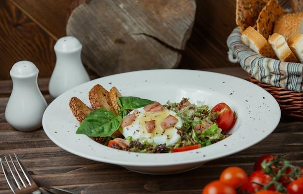 Spiegelei in einer platte mit toast und grünem salat Kostenlose Fotos