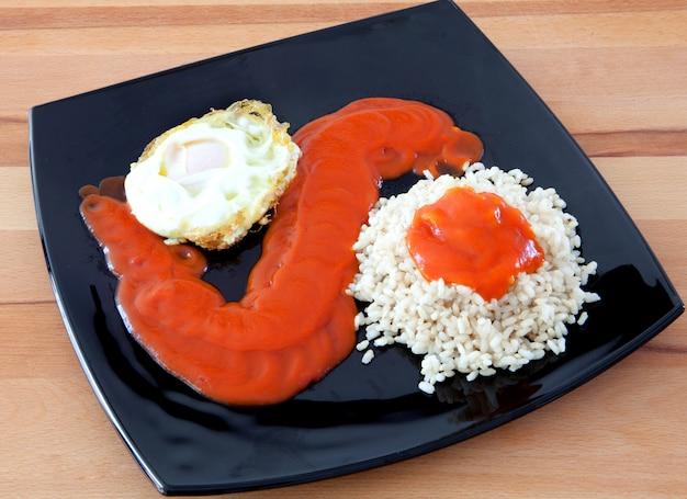 Spiegelei mit gekochtem reis und tomaten Premium Fotos