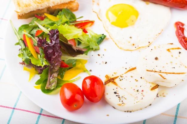 Spiegelei und wurst auf dem teller mit grünem salat und käse Premium Fotos
