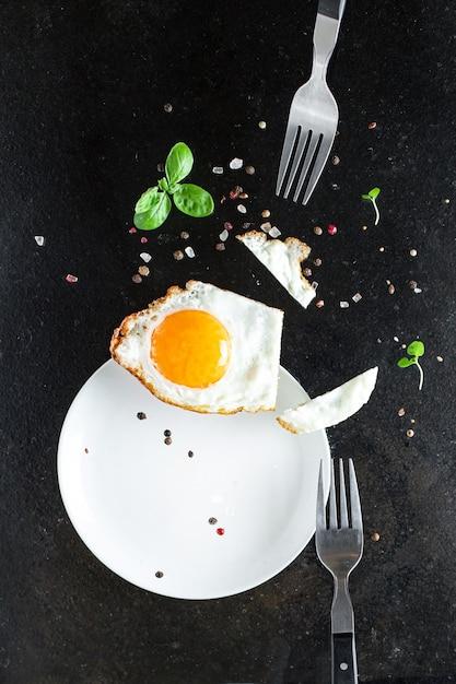 Spiegeleigelb und weiße gabel für lebensmittel omelett frisches gericht und zutaten Premium Fotos