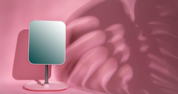 Spiegeln sie auf einer rosa wand mit einem schatten von einem tropischen zimmerpflanzenmonster mit kopienraum Premium Fotos