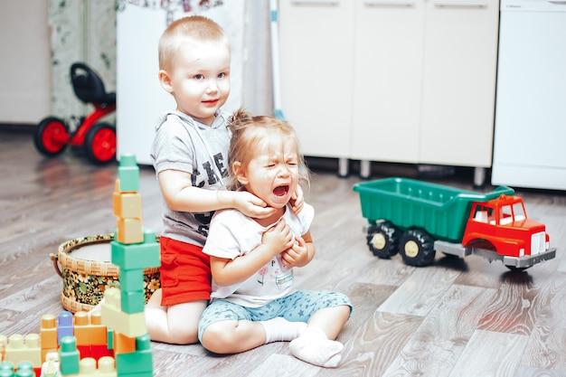 Spiel des kleinen jungen und des mädchens spielt umgekipptes mädchen Premium Fotos