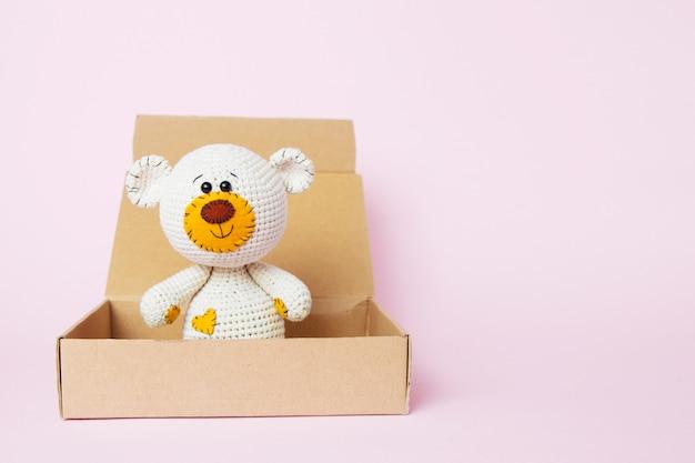 Spielen sie teddybären in einem handwerkskasten, der auf einem rosa hintergrund lokalisiert wird. baby hintergrund. textfreiraum, ansicht von oben Premium Fotos