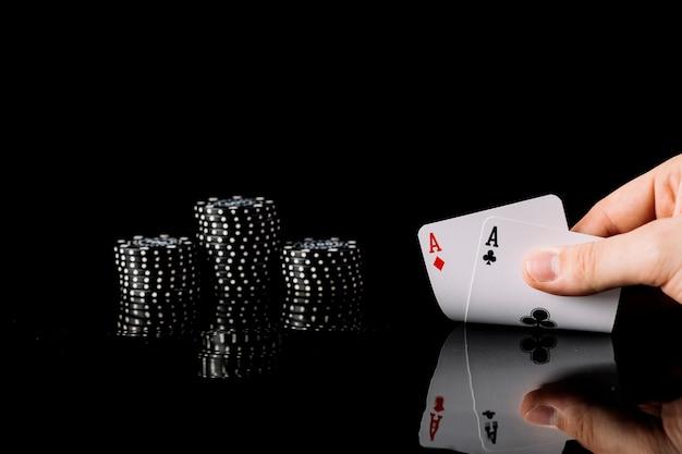 Spieler, der zwei spielkarten der asse nahe chips auf schwarzem hintergrund hält Kostenlose Fotos