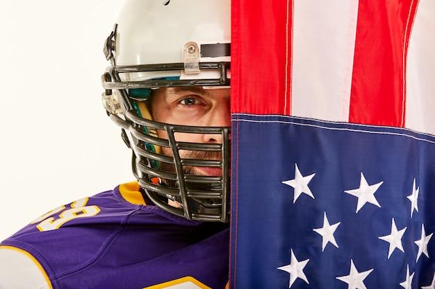 Spieler des amerikanischen fußballs auf hälfte schloss durch amerikanische flagge Premium Fotos