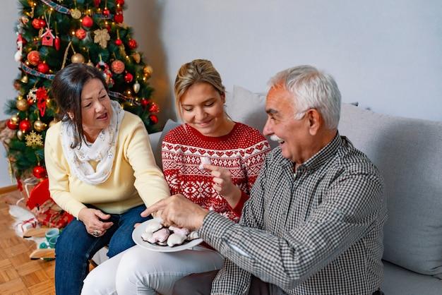 Spielerische familie, die zu hause lebkuchenplätzchen isst. Premium Fotos