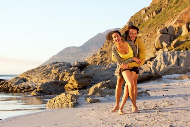 Spielerische junge mischrassepaare am strand Premium Fotos