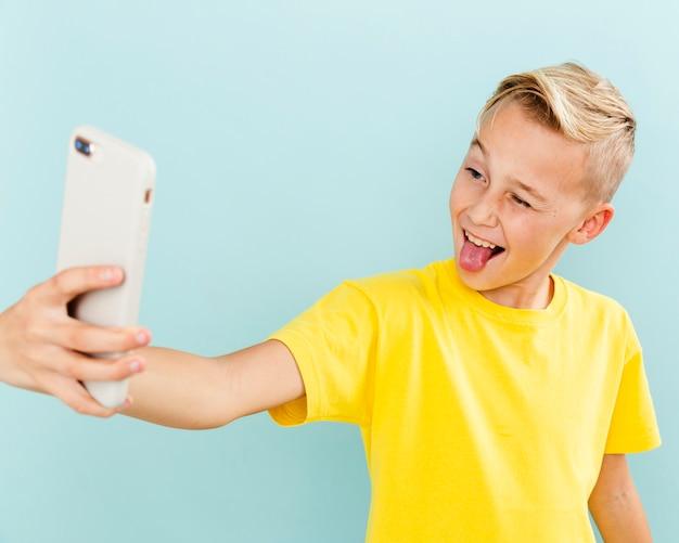 Spielerischer junge der vorderansicht, der selfie nimmt Kostenlose Fotos