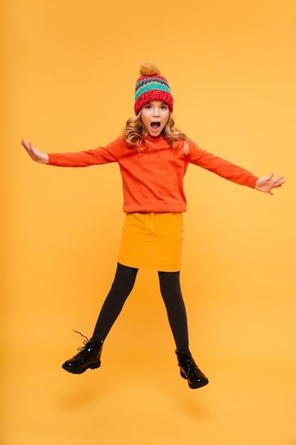 Spielerisches entsetztes junges mädchen in der strickjacke und in hut, welche die kamera über orange springen und betrachten Kostenlose Fotos
