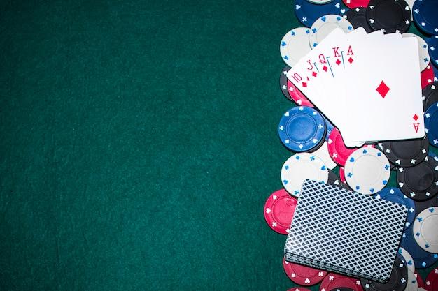 Spielkarte des königlichen errötens über den kasinochips auf grüner pokertabelle Kostenlose Fotos