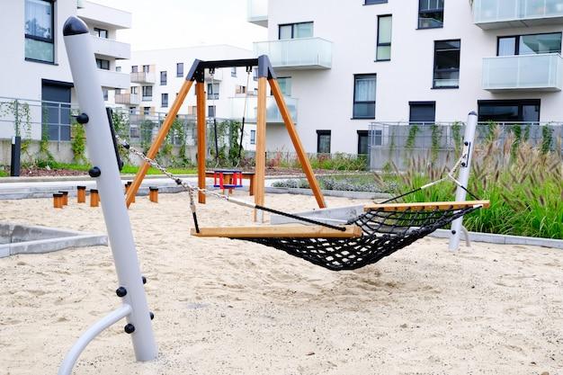 Spielplatz mit hängematte und schaukel im gemütlichen innenhof eines modernen wohnviertels. Premium Fotos