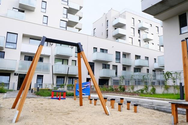 Spielplatz mit schaukel im gemütlichen innenhof eines modernen wohnviertels. Premium Fotos