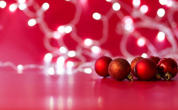 Spielzeug weihnachtskugeln der roten farbe liegen auf einem roten hintergrund Premium Fotos