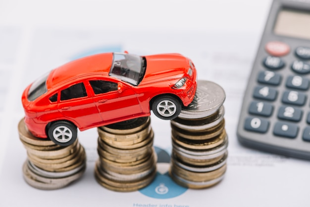 Spielzeugauto, das über dem steigenden münzenstapel balanciert Kostenlose Fotos