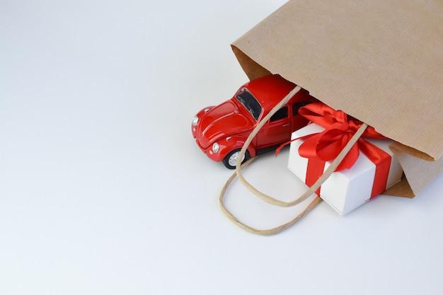 Spielzeugauto mit einer geschenkbox auf dem dach auf einem weißen hintergrund. minimalismus. spielzeuge. das konzept eines geschenks für einen feiertag, geburtstag, weihnachten, ostern. speicherplatz kopieren Premium Fotos