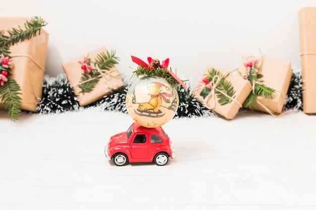Spielzeugauto mit weihnachtskugel nahe präsentkartons Kostenlose Fotos