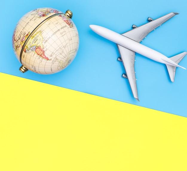 Spielzeugflugzeug reist das weltkugelkonzept auf blau Premium Fotos