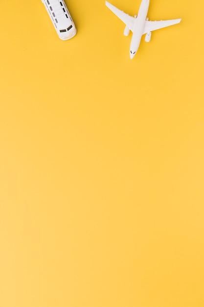 Spielzeugflugzeug und -bus auf orange hintergrund Premium Fotos