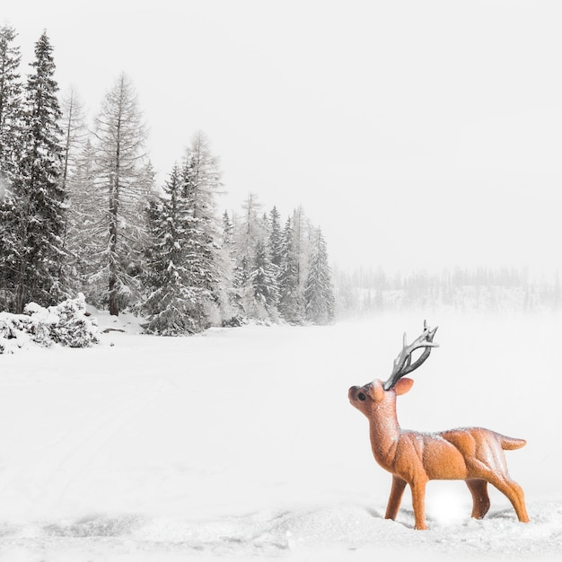 Spielzeugrotwild zwischen feld mit bäumen im schnee Kostenlose Fotos
