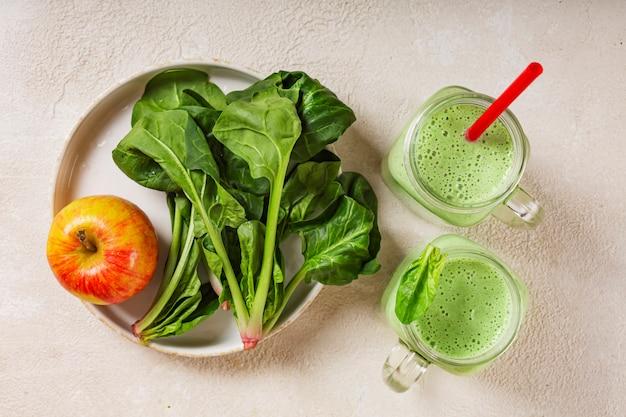 Spinat-joghurt-smoothie mit apfel. saftige spinatblätter und reifer roter apfel. gesundes essen Premium Fotos