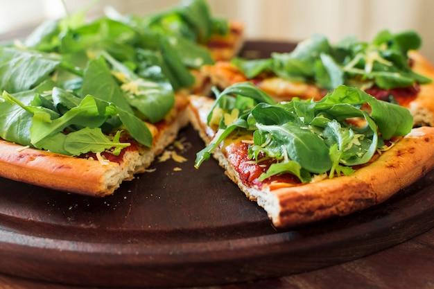Spinatspitzen auf der scheibe der pizza über hölzernem behälter Kostenlose Fotos