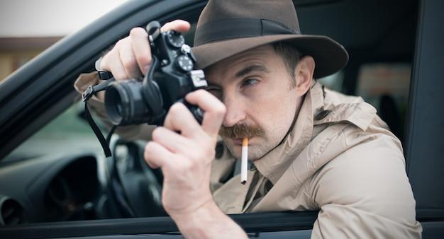 Spion- oder paparazzo-fotograf, mann, der kamera in seinem auto verwendet Premium Fotos