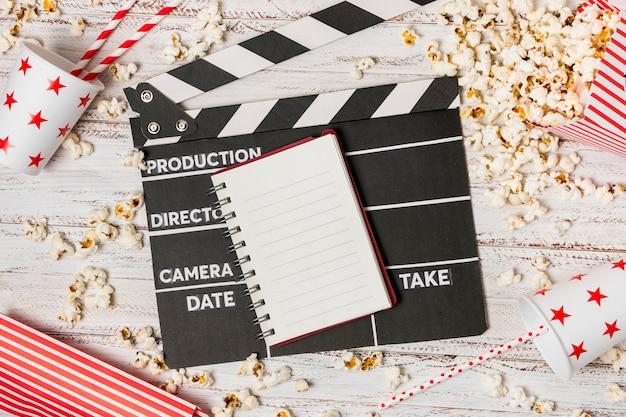 Spiralblock; klappe; trinkhalm und popcorn auf schreibtisch aus holz Kostenlose Fotos