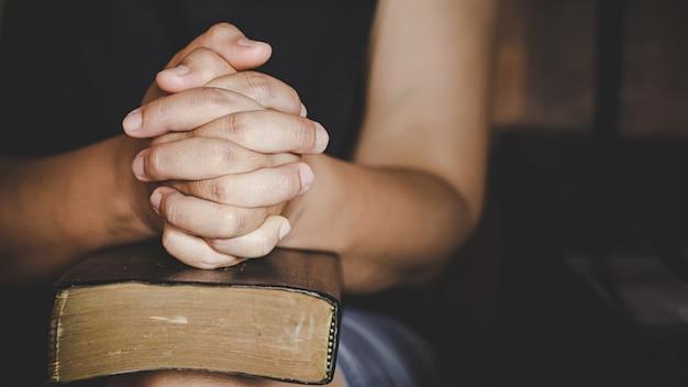 Spiritualität und religion, hände gefaltet im gebet auf einer heiligen bibel in der kirche Kostenlose Fotos
